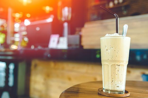 Batido de café batido de leite, bebida gelada e doce com menu de atualização de cafeína na mesa da cafeteria com espaço para texto