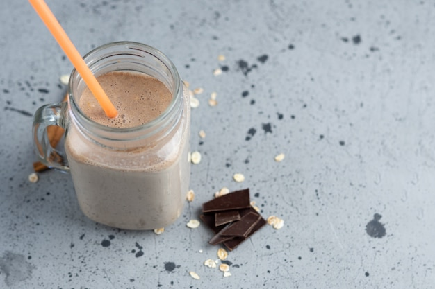 Batido de chocolate com aveia e nozes em uma jarra