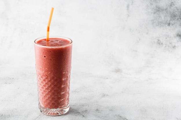 Batido de frutas ou batido de framboesa rosa, vermelho em vidro no fundo de mármore brilhante. visão aérea, copie o espaço. publicidade para o menu de café milkshake. menu de café. foto horizontal.
