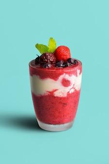 Batido de frutas vermelhas misturado com iogurte, misturando bem em um copo transparente