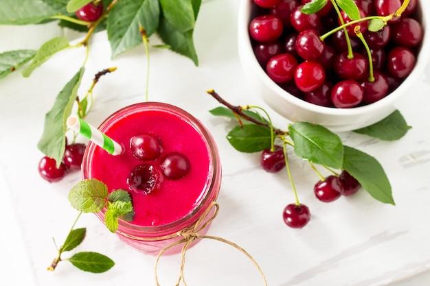 Batido de iogurte de cereja ou batido de leite em frasco de vidro sobre uma mesa de madeira desintoxicação natural