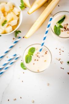 Batido de iogurte, melão amarelo orgânico cru, sementes de linho e hortelã.