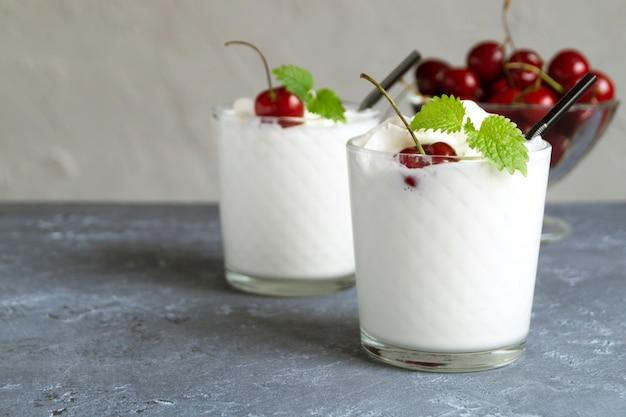 Batido de leite com cerejas. em um fundo cinza.