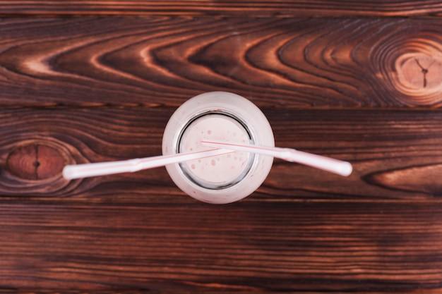 Batido de leite em garrafa na superfície de madeira