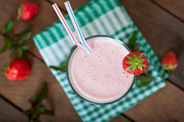 Batido de milk-shake de morango com morango fresco em uma mesa de madeira
