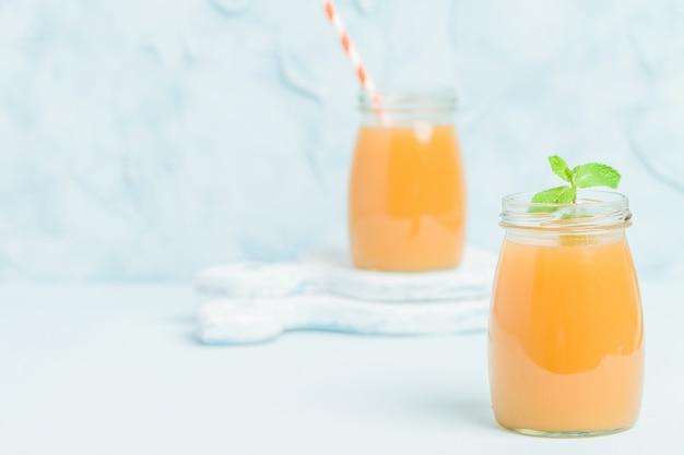 Batido de pêssego em frascos de vidro com folhas de hortelã fresca verde e palhas sobre fundo azul pastel