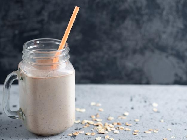 Batido do leite de chocolate com porcas e canela da farinha de aveia. café da manhã saudável