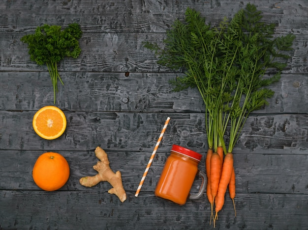 Batido recentemente feito da cenoura, grupo da raiz das cenouras, da laranja e do gengibre em uma tabela escura rústica.