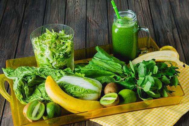 Batido verde misturado com ingredientes no foco seletivo da mesa de madeira.
