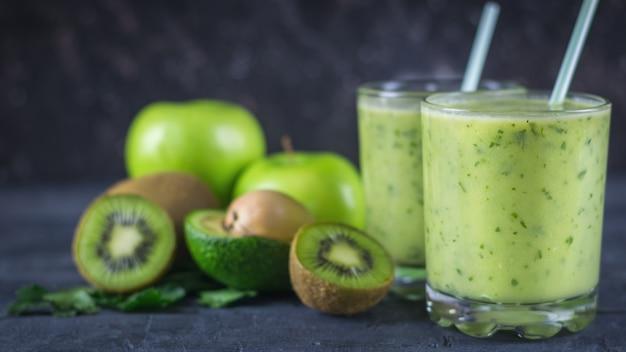 Batidos de abacates, bananas, kiwi e ervas em uma mesa de madeira escura. faça dieta comida vegetariana.