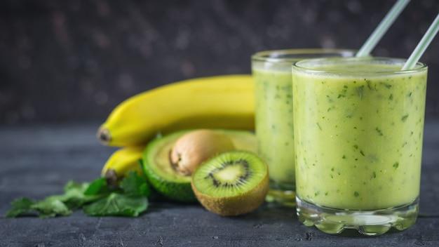 Batidos de abacates, bananas, kiwi e ervas em uma mesa de madeira. faça dieta comida vegetariana.