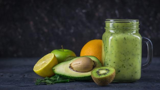 Batidos de abacates, bananas, kiwi e ervas em uma mesa escura de madeira preta. faça dieta comida vegetariana.
