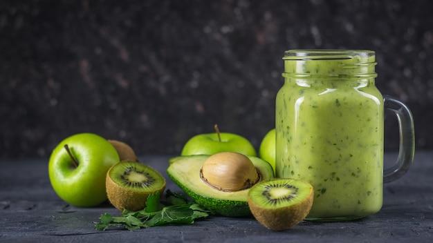 Batidos de abacates, bananas, kiwi e ervas em uma mesa preta. faça dieta comida vegetariana.