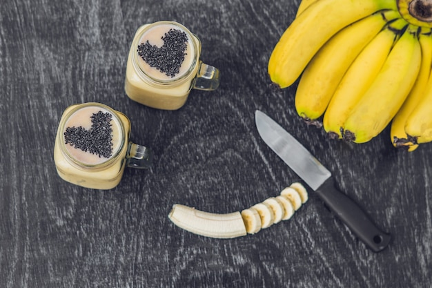 Batidos de banana e bananas em um fundo de madeira velho. Foto Premium