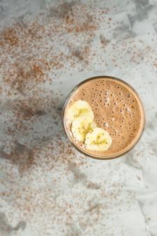 Batidos de chocolate-banana com cacau em um copo sobre um fundo cinza