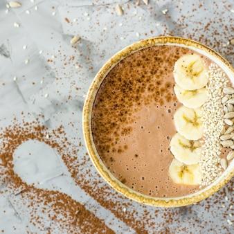 Batidos de chocolate-banana em uma tigela sobre um fundo cinza de concreto