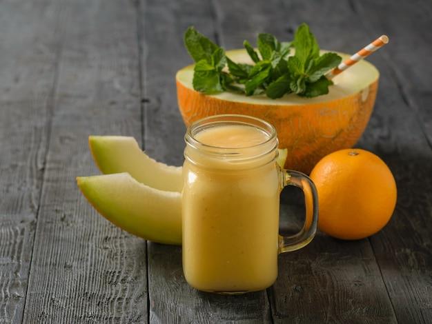 Batidos de melão, laranja e banana recém-feitos e tubos de um coquetel em uma mesa de madeira escura.