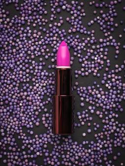 Batom brilhante em uma superfície de bolas roxas no preto