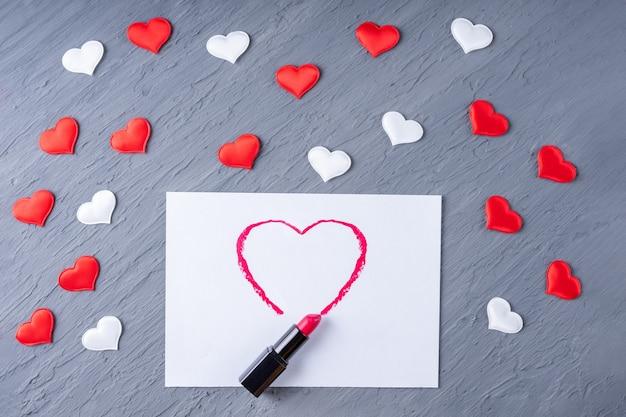 Batom desenha a forma de um coração em papel branco em um fundo cinza