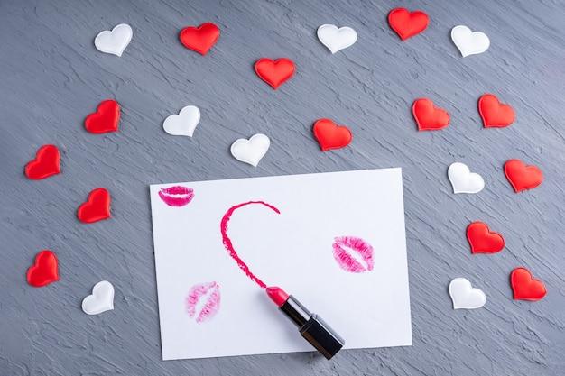 Batom desenha meio coração em papel branco com beijos de batom em um fundo cinza de madeira