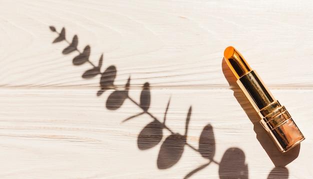 Batom metálico com sombra de folhas