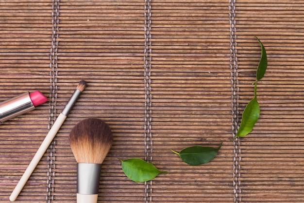 Batom rosa e dois pincéis de maquiagem com folhas verdes no placemat