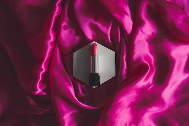 Batom rosa em um fundo de seda texturizado cosméticos de beleza
