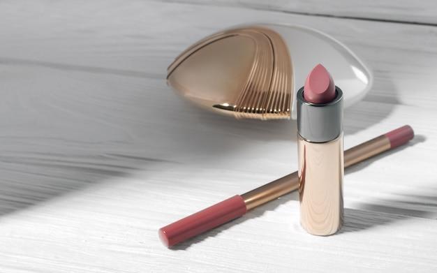 Batom rosa, lápis labial e frasco de perfume de ouro branco na mesa branca