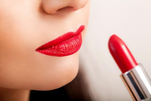 Batom vermelho. close up da cara da mulher com o batom matte vermelho brilhante nos bordos completos. beleza cosméticos, conceito de maquiagem. imagem de alta resolução