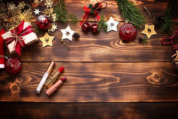 Batom vermelho e brilho labial e pálpebras em um fundo de madeira na decoração de natal. maquiagem de férias para o ano novo, presentes, compras, desejos femininos. espaço para texto, disposição plana