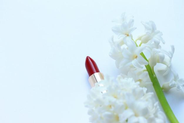Batom vermelho maquiagem e flores em branco