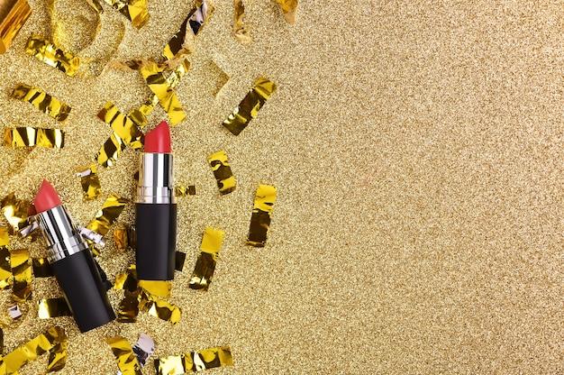 Batom vermelho sobre um fundo dourado brilhante com vista superior do glitter. produto cosmético de beleza feminina para maquiagem profissional.