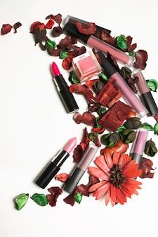 Batons e gloss labial com flores secas sobre fundo branco