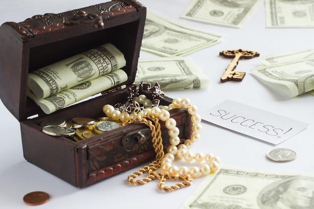 Baú com dinheiro e joias. chave do ícone. a palavra