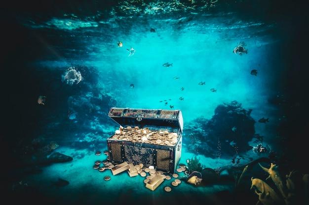 Baú do tesouro contendo barras de ouro e moedas no fundo do mar