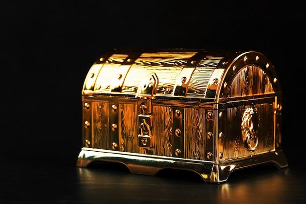 Baú do tesouro de ouro em uma parede preta. caixa fechada com dinheiro e joias. espaço livre, chave baixa