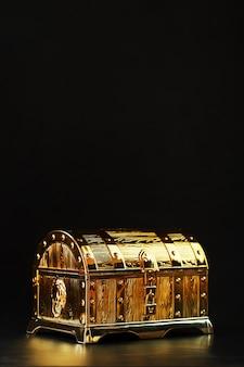 Baú do tesouro de ouro em uma parede preta. caixa fechada com dinheiro e joias. espaço livre, quadro vertical low key