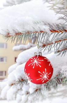 Bauble vermelho em uma árvore de natal ao ar livre