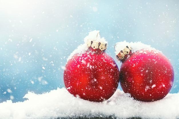 Baubles de natal ou decorações em uma neve em um fundo de inverno brilhante, natal ou conceito de feriados, copie espaço