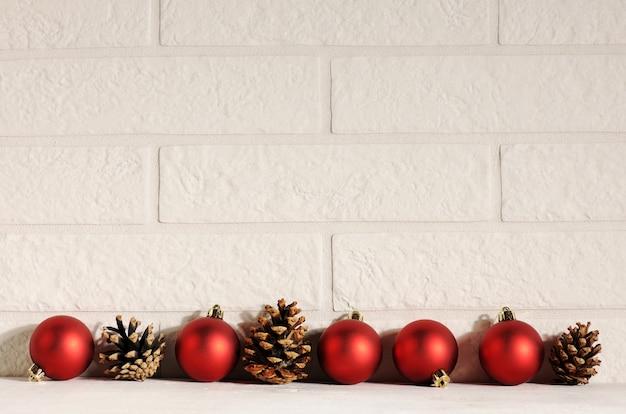 Baubles vermelhos com pinhas em fundo de tijolos brancos