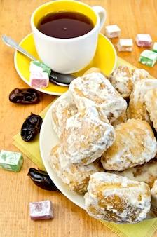 Baursak em um prato, uma xícara de chá com uma colher, de lokum de cor diferente e figos no fundo de tábuas de madeira