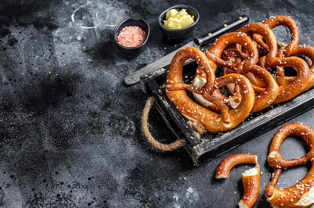 Bávaro pretzels salgados assados em uma bandeja de madeira. fundo preto. vista do topo. copie o espaço.