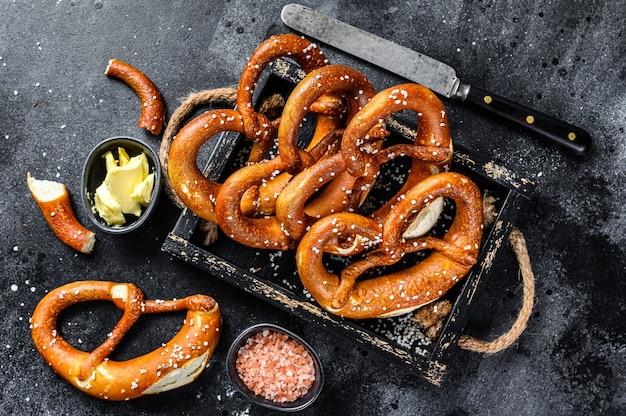 Bávaro pretzels salgados assados em uma bandeja de madeira. fundo preto. vista do topo.