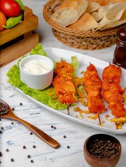 Bbq do peito de frango, no espeto com vegetais, ervas e sumakh e iogurte na placa branca.