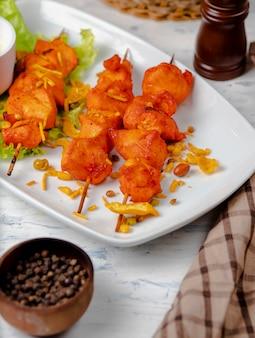 Bbq do peito de frango, no espeto com vegetais, ervas e sumakh na placa branca.