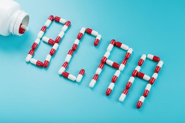 Bcaa de comprimidos vermelhos e brancos de um frasco branco sobre fundo azul