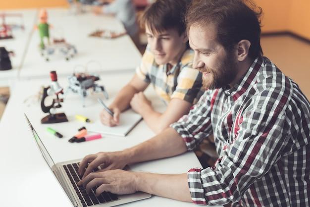 Bearded father help son para programar o robô em casa.