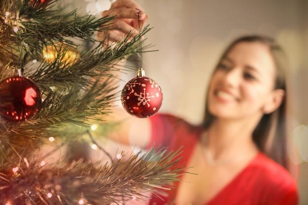 Beautful mulher fazendo a árvore de natal em casa