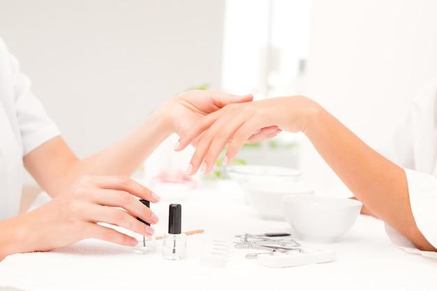 Beautician arquivando clientes do sexo feminino em um salão de beleza de spa