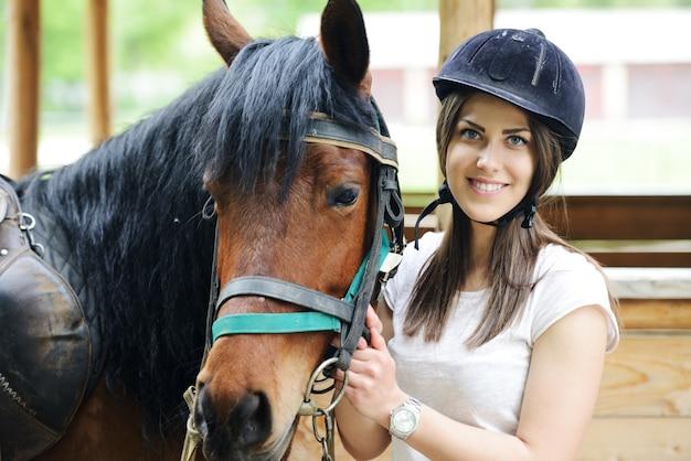 Beautiful girl riding cuidando de um cavalo